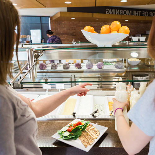 Cornell students select food from the salad bar